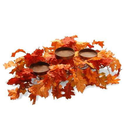 Pile of red and orange leaves with candle holders
