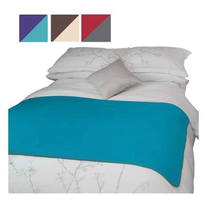 Bed with blue throw on it