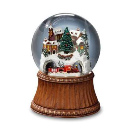 winter village with moving train snow globe