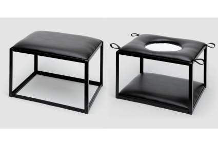 Two black position enhancer chairs, one with a hole in the seat