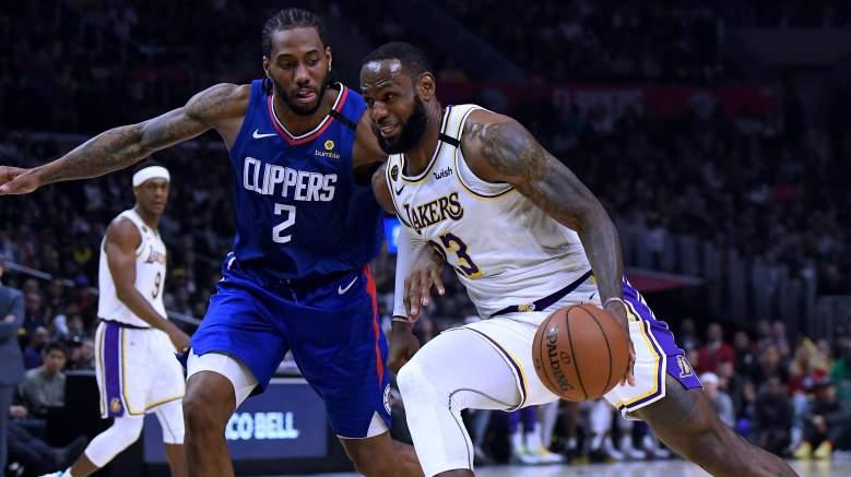 Lakers star LeBron James, at right, drives past Clippers forward Kawhi Leonard