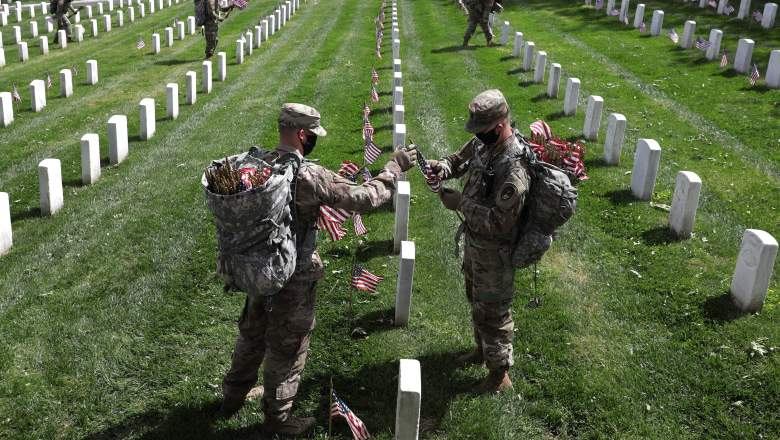 """Soldiers from the 3rd Infantry Regiment, also called the """"Old Guard,"""" place U.S. flags in front of every grave site ahead of the Memorial Day weekend in Arlington National Cemetery"""