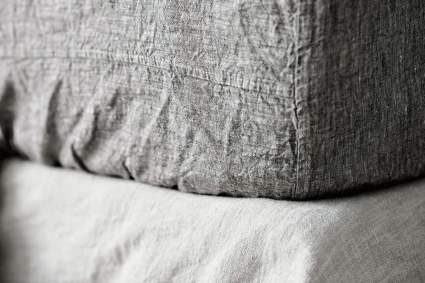 Bed with grey Beflax sheet made of linen