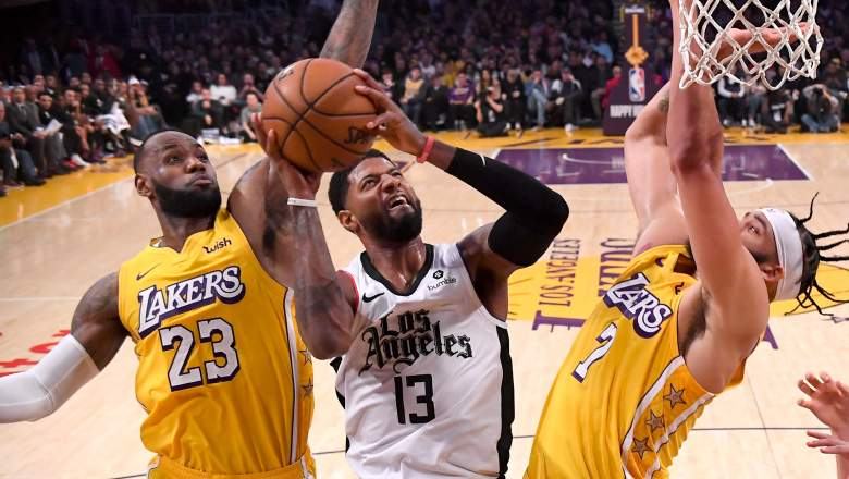Paul George of the Clippers (center) goes up as LeBron James of the Lakers (left) and JaVale McGee attempt a blocked shot