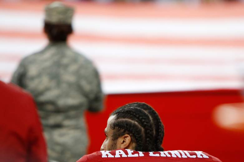 Colin Kaepernick silent protest with veteran in background