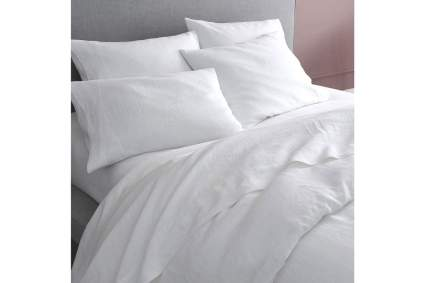 Comfortable looking bed covered in white sheets
