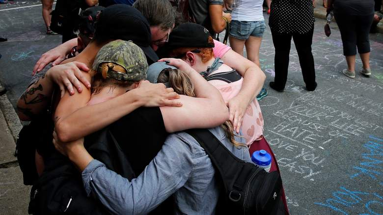 """Members of the Charlottesville community and protest groups mourn near a makeshift memorial for Heather Heyer, who was killed one year ago during a deadly clash, August 12, 2018 in Charlottesville, Virginia. Charlottesville has been declared in a state of emergency by Virginia Gov. Ralph Northam as the city braces for the one year anniversary of the deadly clash between white supremacist forces and counter protesters over the potential removal of Confederate statues of Robert E. Lee and Jackson. A """"Unite the Right"""" rally featuring some of the same groups is planned for Washington, DC."""