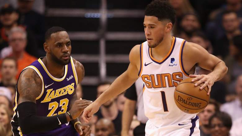 Devin Booker, Suns, at right as Lakers forward LeBron James defends