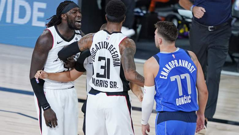 Montrezl Harrell, far left, confronts the Mavericks' Luke Doncic (No. 77) during Game 3 of thier first-round playoff series.