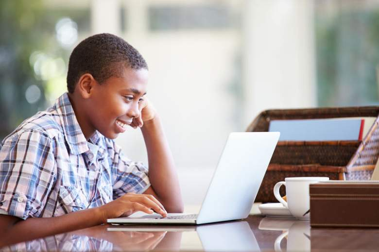 A boy of middle school age using a laptop
