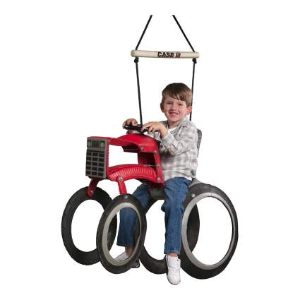 Boy on red tractor shaped tire swing