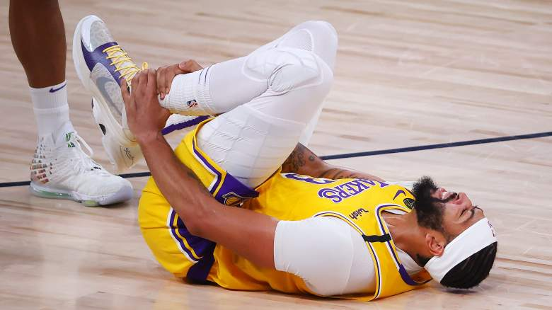 Anthony Davis, Lakers, holds his injured left ankle.
