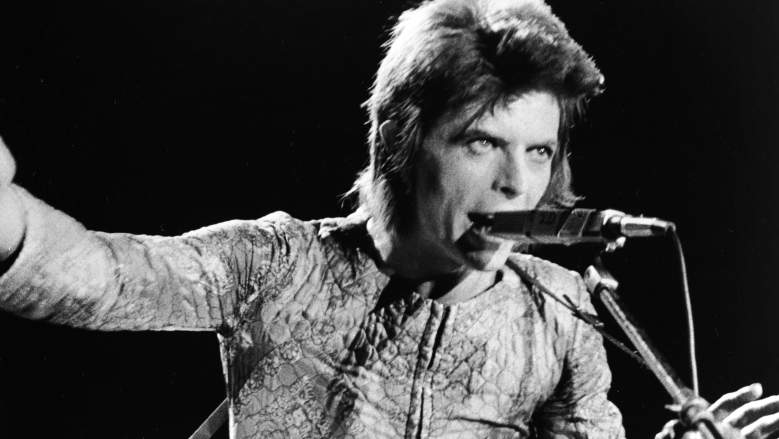 British rock singer David Bowie performs with an acoustic guitar on stage, in costume as 'Ziggy Stardust,' circa 1973.