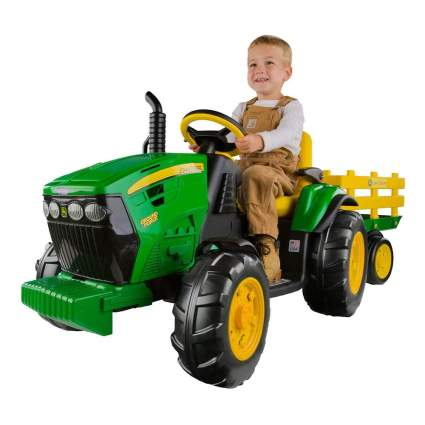 Boy on motor powered green tractor