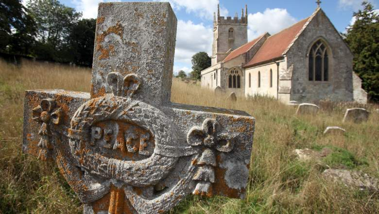 The sun illuminates a grave stone in the churchyard of St Giles in the village of Imber.