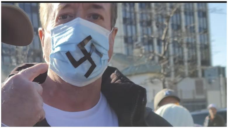 man with swastika mask