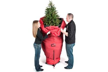 Couple storing their Christmas tree in a red bag