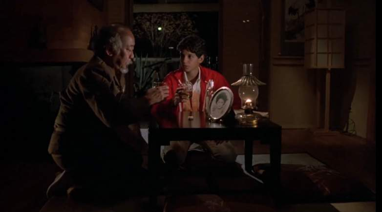 Daniel (Ralph Macchio) sits with a drunken Mr. Miyagi (Pat Morita) in The Karate Kid.