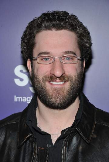 Dustin Diamond smiling while wearing glasses.