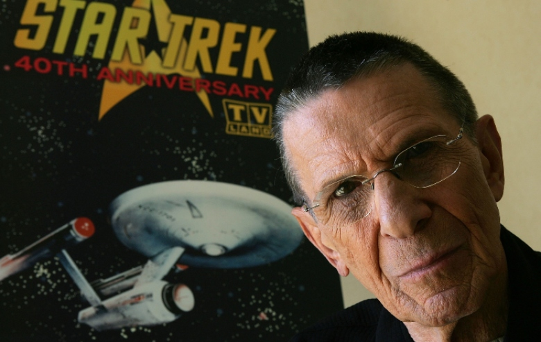 Leonard Nimoy poses in front of a vintage Star Trek poster