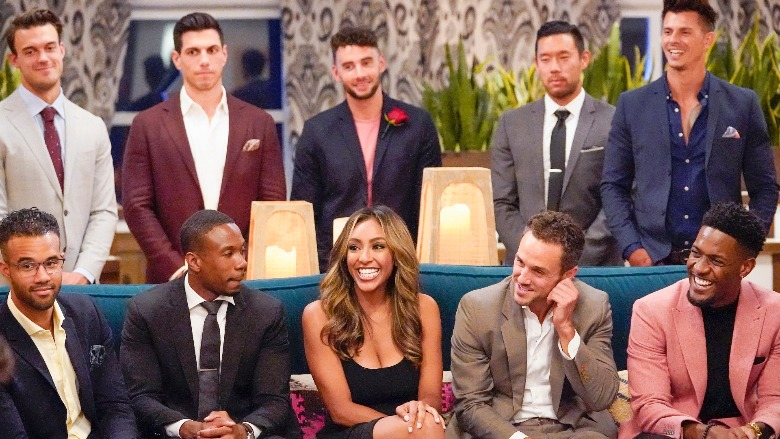 Tayshia Adams sits on a couch with a few men from her season.