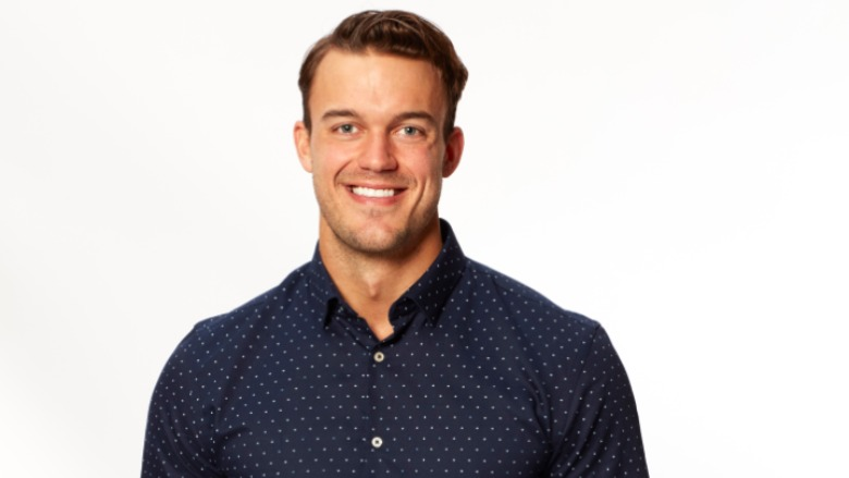 Ben Smith poses wearing a blue collared shirt.