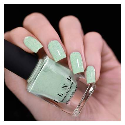 Light creamy green nail polish swatched with bottle