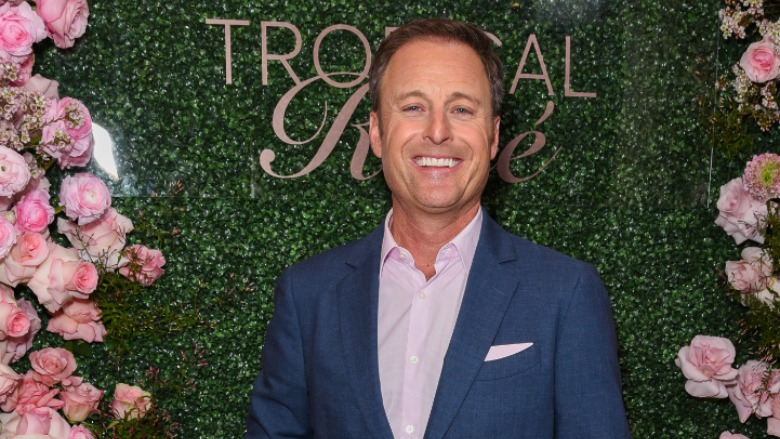 Chris Harrison standing in front of a rose wall.