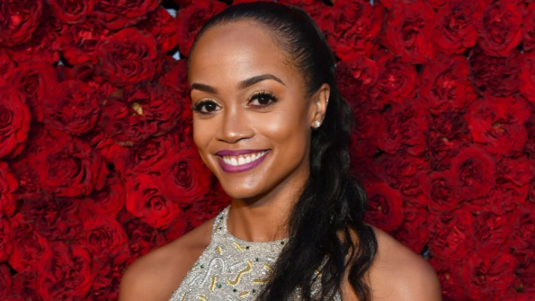 Rachel Lindsay standing in front of a red rose wall.