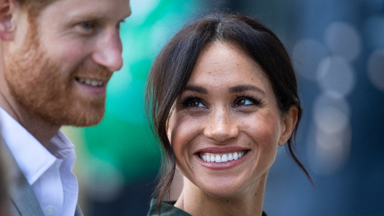 Meghan Markle smiles as she looks at Prince Harry.