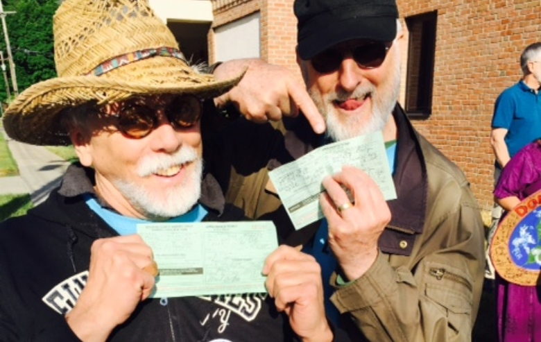 """JG Hertzler and Jamie Cromwell participated in an ant-fracking protest. They are pictured here, each holding his """"notice to appear"""""""