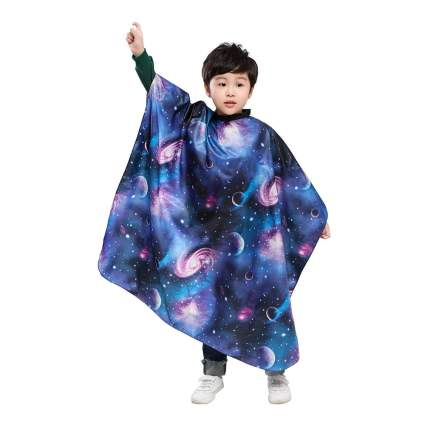 Young child in galaxy-themed hairstyling cape