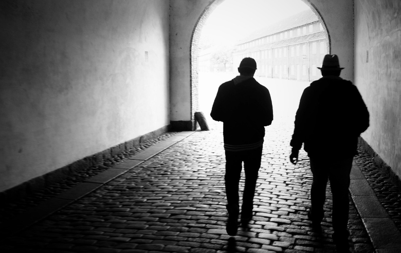 Two people in silhouette walking through a tunnel