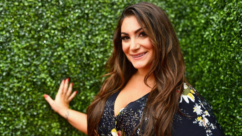 Deena Cortese standing in front of a grass wall.