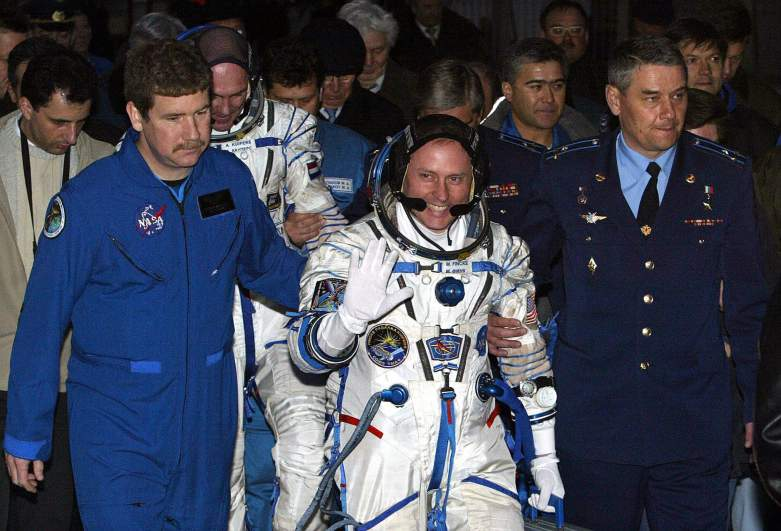 US astronaut Edward Michael Fincke (C) escorted by Russian officers as Dutch ESA astronaut Andre Kuipers (L) follows him during a farewell ceremony at the launch pad of Baikonur cosmodrome, 19 April 2004.