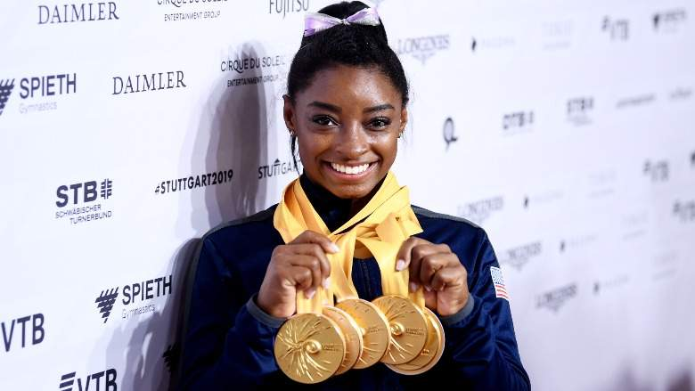 Simone Biles with her medals around her neck.