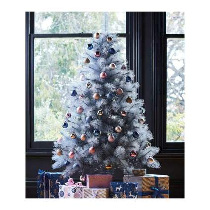 silver glitter holiday tree with ornaments and gifts