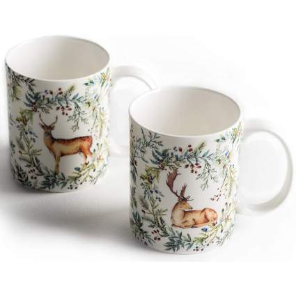 Two coffee mugs with deer and holly